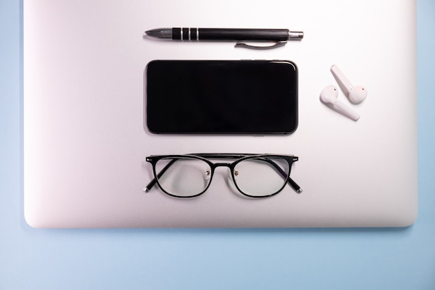 Sur un fond coloré, ordinateur portable, lunettes, stylo, casque, vue de dessus. concept d'entreprise.