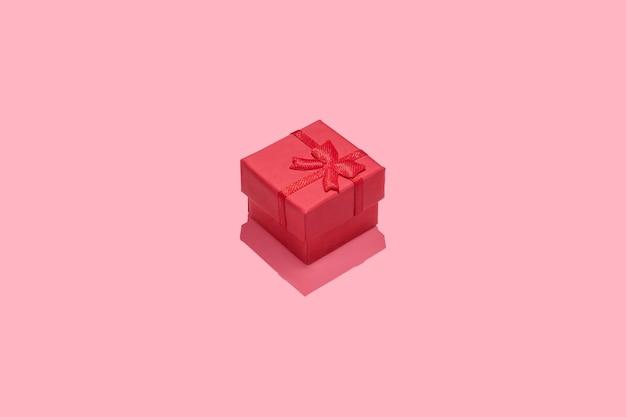 Fond de composition minimale avec boîte-cadeau rouge sur fond rose.