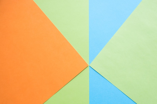 Fond de composition plate de géométrie de papiers de couleur avec des tons verts orange et bleus