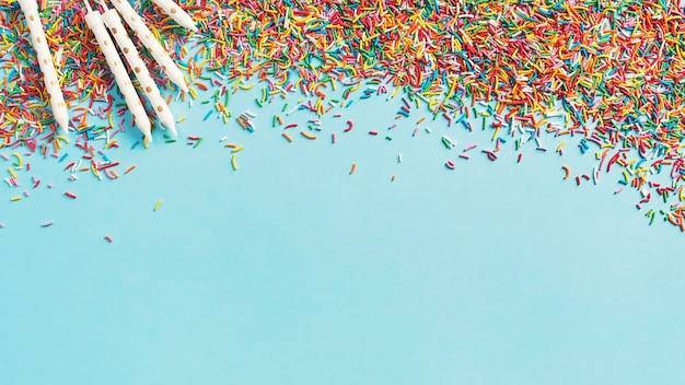 Fond de concept anniversaire et fête avec des confettis et des bougies sur bleu, vue de dessus, espace copie, bannière