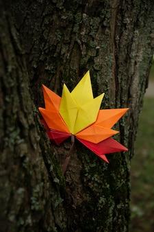 Fond de concept d'automne artisanat en papier traditionnel origami à la main feuilles d'érable tombées nature image de fond coloré parfait pour une utilisation saisonnière sur le tronc