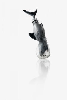 Fond de concept créatif par photo de requin (modèle de jouet) coincé dans une bouteille en plastique bleue transparente, avec espace de copie.