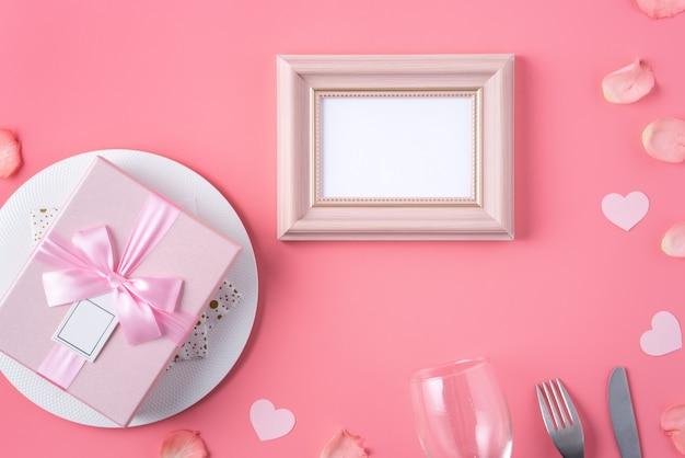 Fond de concept de design saint valentin avec pétales roses et boîte-cadeau sur rose