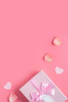 Fond de concept de design saint valentin avec pétales roses et boîte-cadeau