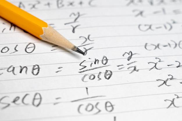 Fond de concept éducatif avec des formules mathématiques et des crayons.