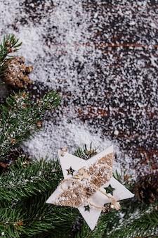 Fond de concept de noël, décoration étoile à la main et arbres de noël verts sur une table en bois, parsemé de neige blanche