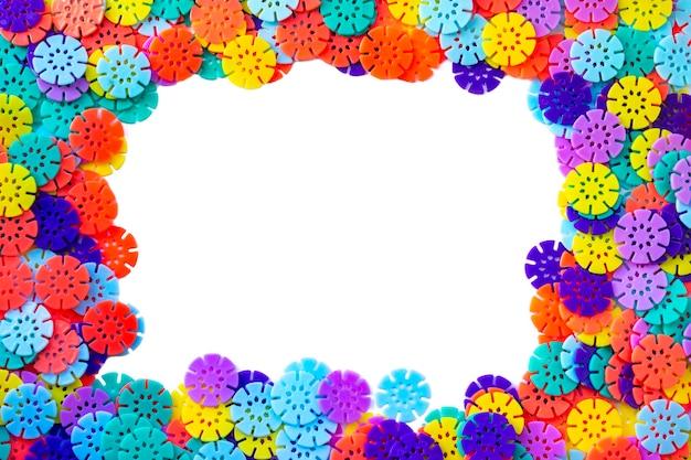 Fond de concepteur de cadre multicolore. détails multicolores en forme de flocons de neige du designer pour enfants sur fond blanc. disques en plastique pour le développement de la motricité fine de la nageoire