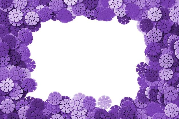 Fond de concepteur de cadre violet. détails multicolores en forme de flocons de neige du designer pour enfants sur fond blanc. disques en plastique pour le développement de la motricité fine des doigts.