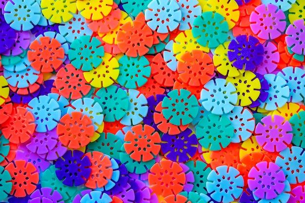 Fond de concepteur multicolore. détails multicolores en forme de flocons de neige du créateur pour enfants. disques en plastique pour le développement de la motricité fine des doigts.