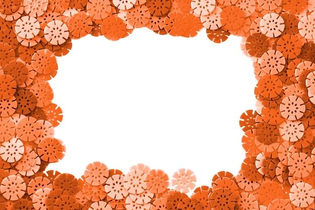 Fond de concepteur orange. détails orange en forme de flocons de neige du designer pour enfants sur fond blanc. disques en plastique pour le développement de la motricité fine des doigts.
