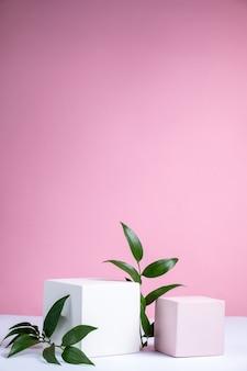 Fond cosmétique avec des formes géométriques sur fond rose deux podiums cubiques et maquette de fond abstrait de feuilles vertes pour la démonstration de produits cosmétiques