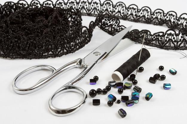 Fond de couture: ciseaux en métal, fils noirs, dentelle et perles