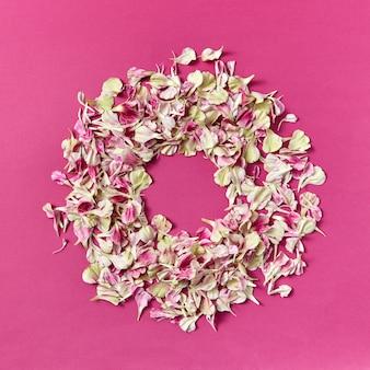 Fond créatif avec cadre floral rond de pétales d'oeillet sur un espace violet, copie. mise à plat.