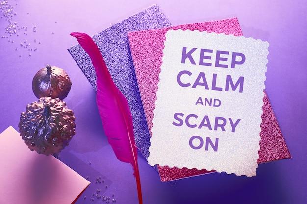 Fond créatif halloween violet et rose, texte restez calme et effrayant. plume d'épingle rose, cartes scintillantes et citrouilles