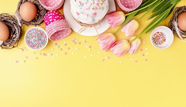 Fond créatif de vacances de pâques avec gâteau de pâques, oeufs dans les nids, tulipes et décorations vue de dessus à plat avec espace de copie