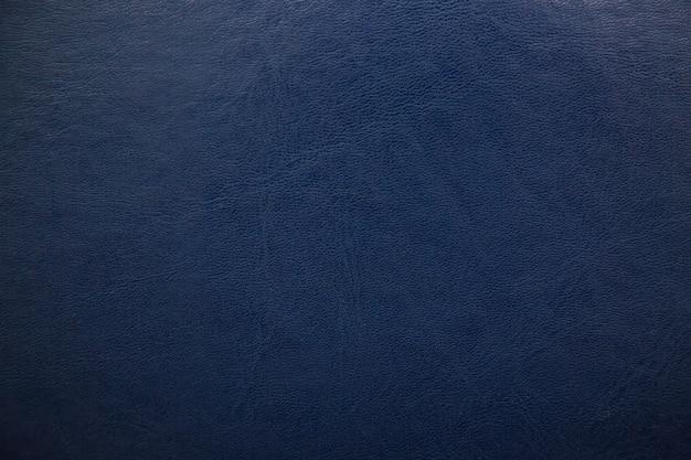 Fond en cuir texturé bleu foncé.