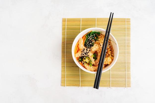 Fond de cuisine asiatique avec bol de crevettes épicé poke avec du riz, des algues et des graines de sésame, avocat avec des baguettes sur blanc. bol de bouddha. déjeuner de fruits de mer sain. nourriture diététique. vue de dessus avec espace copie.