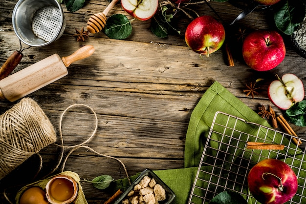 Fond de cuisine automne, concept de cuisson de tarte aux pommes, pommes rouges fraîches, épices douces, sucre, farine, rouleau à pâtisserie, œufs, ustensiles de cuisson, fond en bois