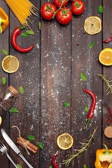 Fond de cuisine en bois avec des herbes et épices éparpillées et copiez l'espace