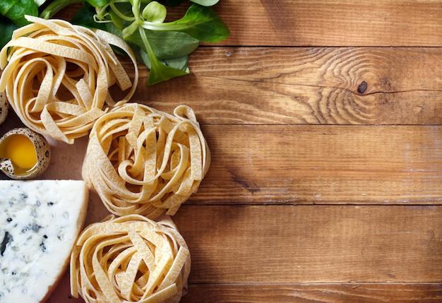 Fond de cuisine italienne sur des planches en bois rustique avec fond, avec des pâtes tagliatelles, des tomates, du basilic, du fromage, des grossini et des condiments