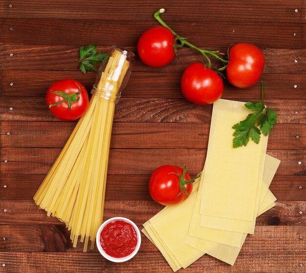 Fond de cuisine italienne sur des planches de bois rustiques avec fond, avec pâtes tagliatelles, tomates, basilic, fromage, grossini et condiments