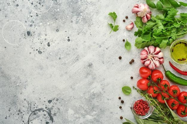 Fond de cuisson des aliments. safran frais, ail, coriandre, basilic, tomates cerises, poivrons et huile d'olive, épices, herbes et légumes sur une table en ardoise gris clair. vue de dessus des ingrédients alimentaires.