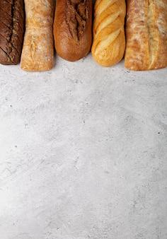 Fond de cuisson avec diverses miches de pain entières fraîchement cuites à plat sur une surface grise avec espace de copie