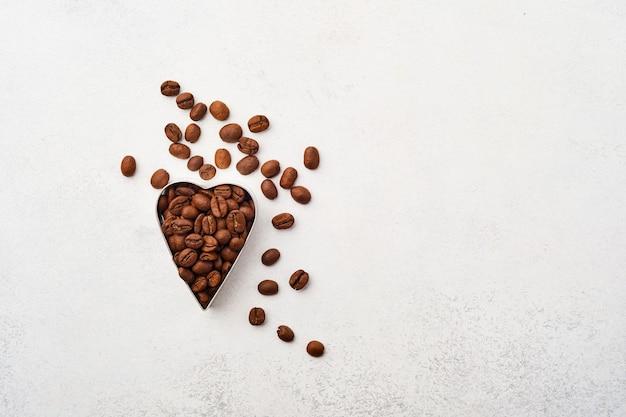 Fond de cuisson avec emporte-pièces et grains de café sur fond gris.