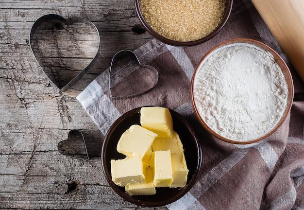 Fond de cuisson avec de la farine, du sucre, du beurre, un rouleau à pâtisserie, des oeufs et une forme de coeur