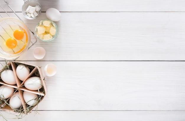 Fond de cuisson. ingrédients de cuisson pour la pâte, les œufs et le beurre sur bois rustique blanc. vue de dessus, recette ou cours de cuisine.