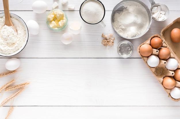 Fond de cuisson. ingrédients de cuisson pour pâte et pâtisserie, œufs, farine et beurre sur bois rustique blanc. vue de dessus