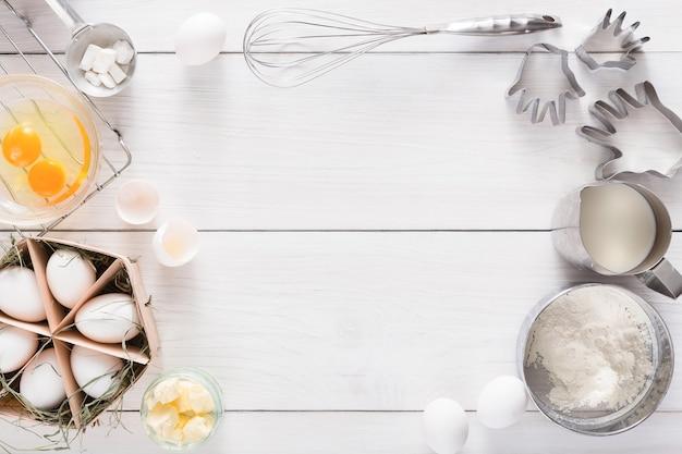 Fond de cuisson. ingrédients de cuisson pour pâte et pâtisserie, œufs, farine et emporte-pièce sur bois rustique blanc. vue de dessus