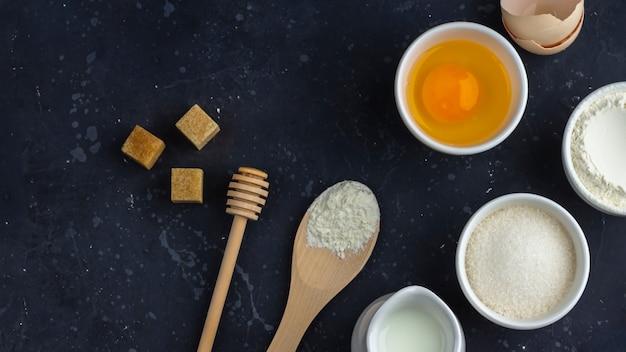 Fond de cuisson. ingrédients pour la cuisson du gâteau (farine, œuf, sucre, lait) dans des bols sur une table sombre. concept alimentaire. vue de dessus, mise en page plate, espace de copie pour le texte.