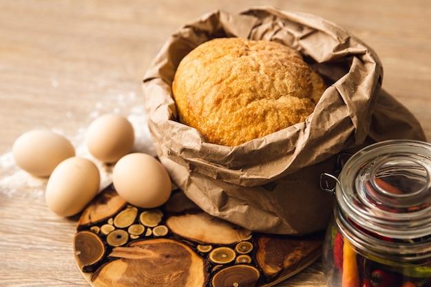 Fond de cuisson avec des œufs et du pain dans un sac en papier