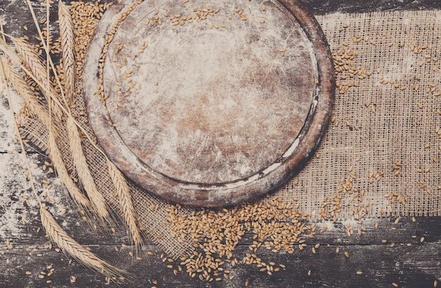 Fond de cuisson de pain. du grain et des épis éparpillés sur du bois rustique près d'un bureau rond en bois saupoudré de farine. récolte de blé agricole, composition de fabrication de pain