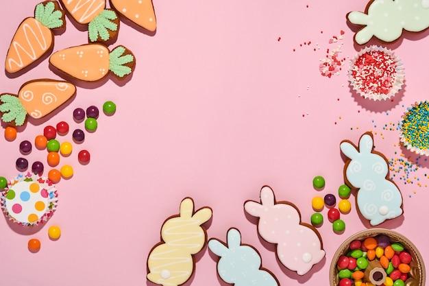 Fond de cuisson de pâques. pain d'épice multicolore de pâques, bonbons, garniture de confiserie dispersée et boîte-cadeau sur fond rose.