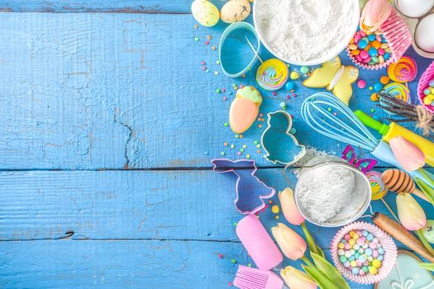 Fond de cuisson de pâques avec rouleau à pâtisserie, fouet, œufs, farine et confettis de sucre colorés