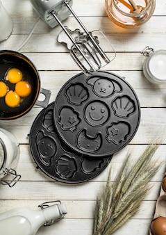 Fond de cuisson. préparation de la pâte pour de délicieux biscuits. sur un fond en bois blanc.