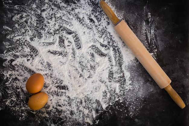 Fond de cuisson avec le rouleau à pâtisserie avec de la farine. sur la table noire