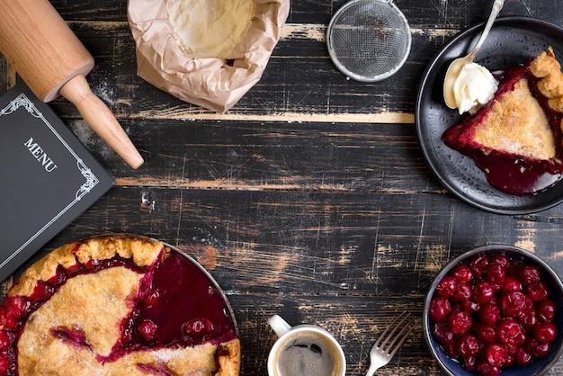 Fond de cuisson avec tarte aux cerises en tranches, farine, rouleau à pâtisserie et tableau de menu sur table en bois