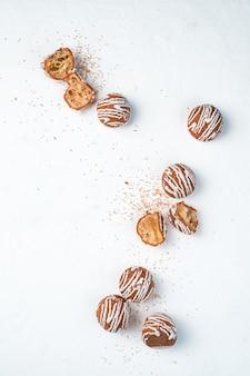 Fond culinaire abstrait avec de petits biscuits bruns ronds disposés sur un fond blanc.