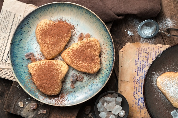 Fond culinaire avec des biscuits en forme de coeur sur fond vintage.