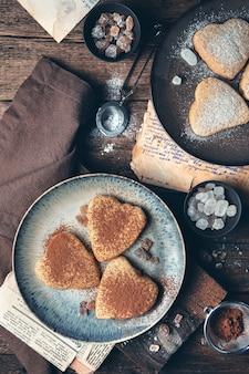 Fond culinaire avec des cookies en forme de coeurs sur un fond vintage.