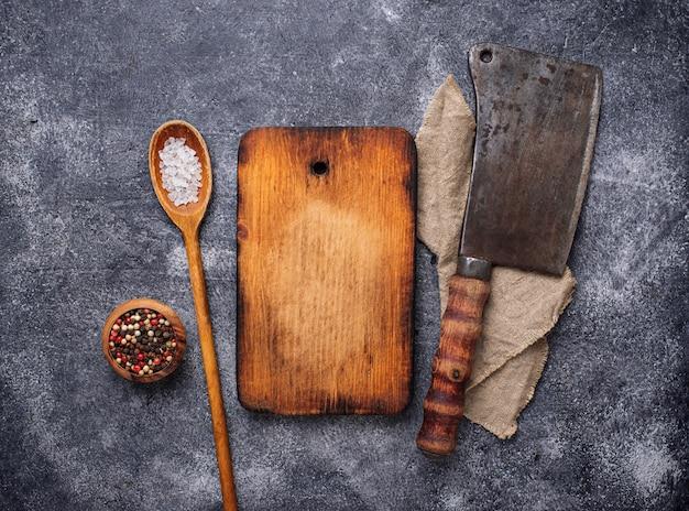 Fond culinaire avec des épices, planche à découper et hachette