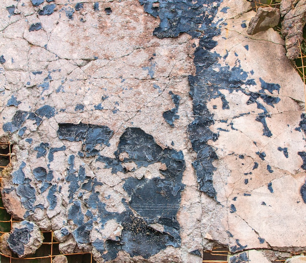 Fond d'une dalle de béton avec de la peinture fissurée.
