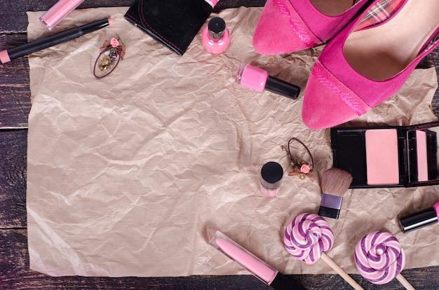 Fond de dames - tulipes roses, chaussures, rouge à lèvres, vernis à ongles, boucles d'oreilles, blush, sucettes sur papier kraft