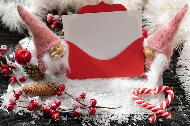 Fond décoratif de noël avec une enveloppe de noël rouge et une feuille blanche vierge