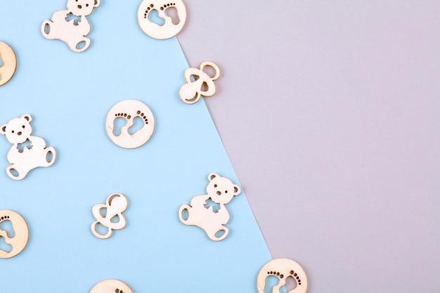 Fond décoratif pastel minimal avec de petites figures en bois pour l'anniversaire du nouveau-né