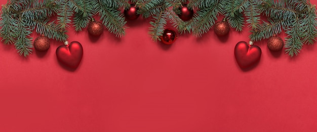 Fond de décoration de noël de boules rouges et coeur, branches à feuilles persistantes sur le rouge. vue d'en haut, pose à plat. noël.
