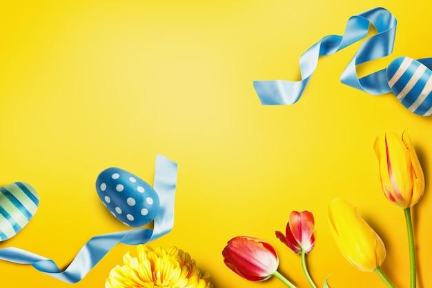Fond de décoration de pâques avec ruban d'oeufs colorés et fleurs dans un style jaune